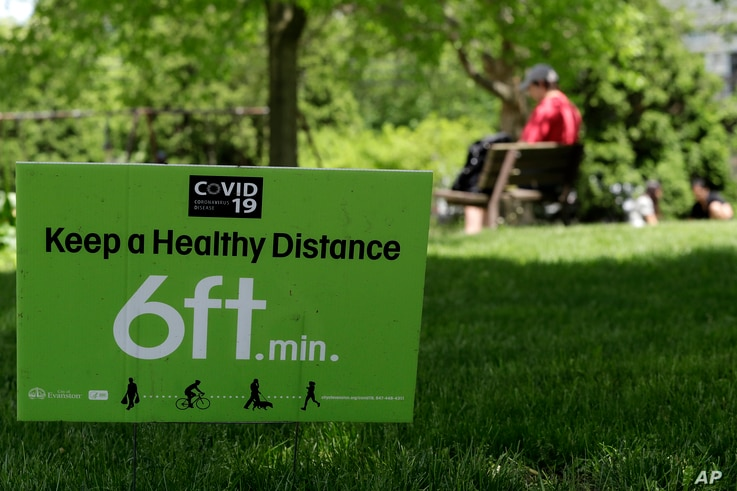 A sign is seen at Independence Park in Evanston, Ill., Friday, May 29, 2020. Every region of Illinois met the criteria to move…