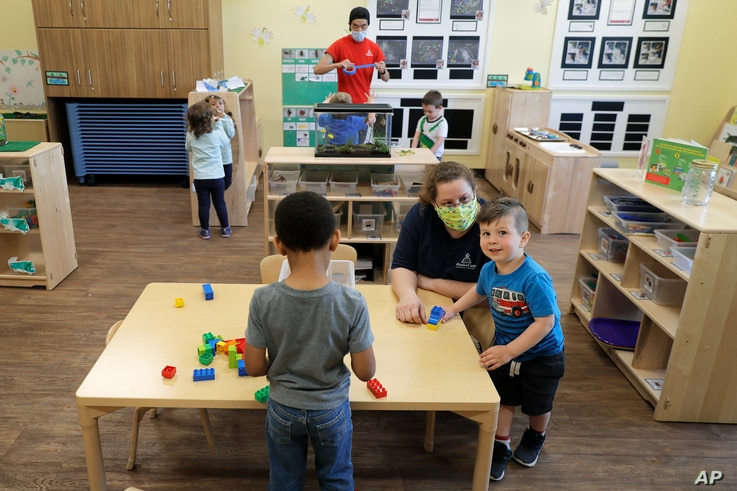In this May 27, 2020, photo, teachers Jana Blair, right, and Aaron Rainboth, upper-center, wear masks as they work with kids at…