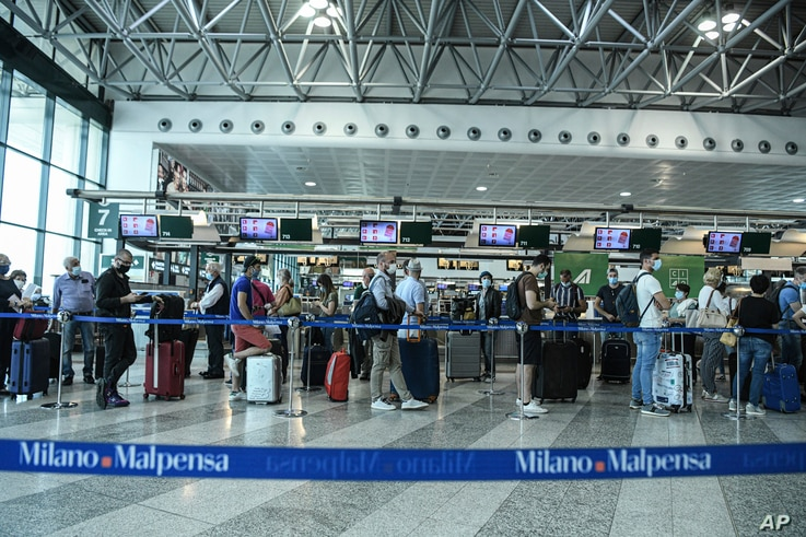 Passengers line up to at the check-in gates, at the Milan Malpensa airport Monday, June 15, 2020. Borders opened up across…