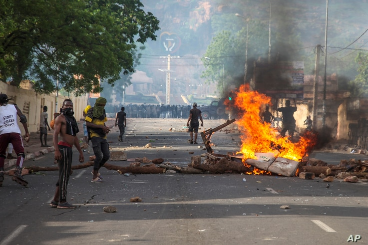 In this photo taken Friday, June 19, 2020, protesters demanding President Ibrahim Boubacar Keita's resignation stand by a…