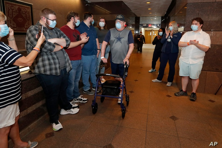 COVID-19 patient Stephen Donelson is applauded by family and health care professionals as he departs the Zale Hospital on the…
