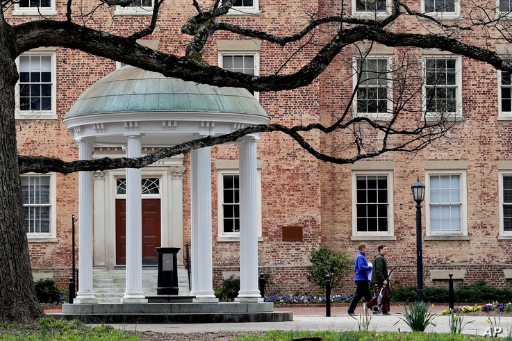 FILE - In this March 18, 2020, file photo, people remove belongings on campus at the University of North Carolina in Chapel…