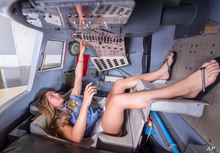 FILE- Tara Clemenceau, 11, visiting from France, tries her hand at the controls of a Mercury space capsule at the U.S. Space &…