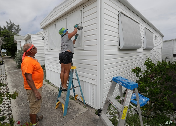 Chris Nagiewicz, left, watches as his wife Mary screws in a hurricane panel, Saturday, Aug. 1, 2020, on a trailer home in Briny…