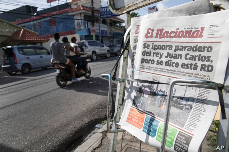 A motorbike rides past a newsrack displaying copies of El Nacional newspaper with a page one headline that reads in Spanish: …