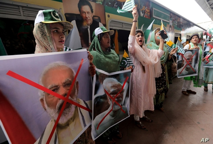 Women hold crossed out portrait of Indian Prime Minister Narendra Modi as they participate in a train march to mark the first anniversary of India's decision to revoke the disputed region's semi-autonomy, in Karachi, Pakistan, Aug. 5, 2020.