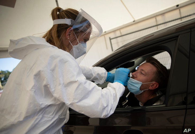A healthcare worker demonstrates a nasal swab on a patient during a test day at a drive-thru COVID-19 testing site in Antwerp,…