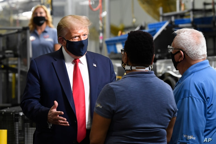 President Donald Trump wears a mask as he talks with employees as he tours the Whirlpool Corporation facility in Clyde, Ohio,…
