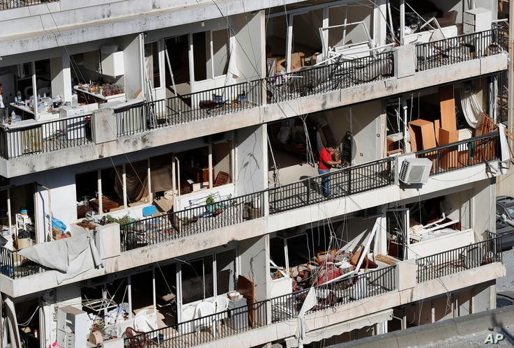 A man stands on his apartment balcony of a building damaged by Tuesday's explosion that hit the seaport of Beirut, Lebanon,…