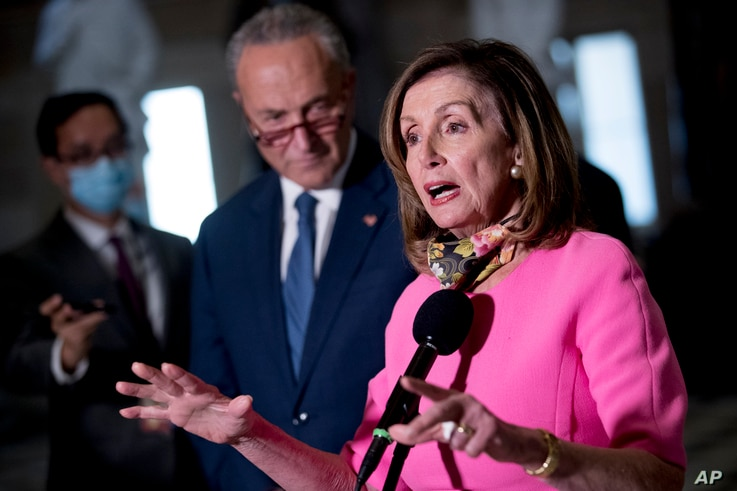 House Speaker Nancy Pelosi of Calif., center, accompanied by Senate Minority Leader Sen. Chuck Schumer of N.Y., left, speak to…