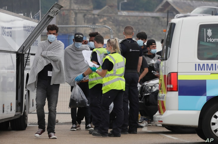 Border Force officers escort a group of men thought to be migrants to a waiting bus in the port city of Dover, England, Aug. 8, 2020.
