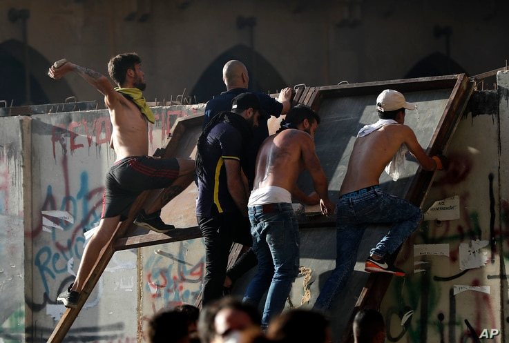 Anti-government protesters climb concrete wall that installed by security forces and throw stones against the army, as they try to reach the Parliament building, during a protest against the political elites and the government, Beirut, Aug. 8, 2020.