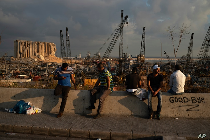 People sit near the site of last week's explosion that hit the seaport of Beirut, Lebanon, Aug. 11, 2020.