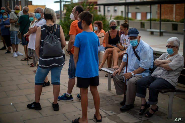People wearing face masks wait their turn to be called for a PCR test for the COVID-19 outside a local clinic in Santa Coloma…