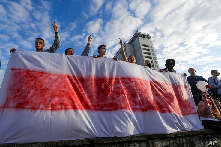 People hold a handmade banner of an old Belarusian national flag as they gather to protest against the results of the country's…