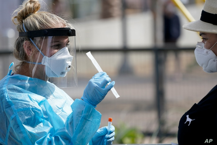Nurse practitioner Debbi Hinderliter, left, collects a sample from a woman at a coronavirus testing site near the nation's…