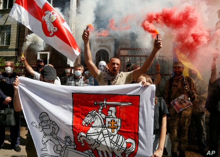 People, some of them ethnic Belarusians, light flares and wave Belarusian flags to support Belarusian opposition in front of…