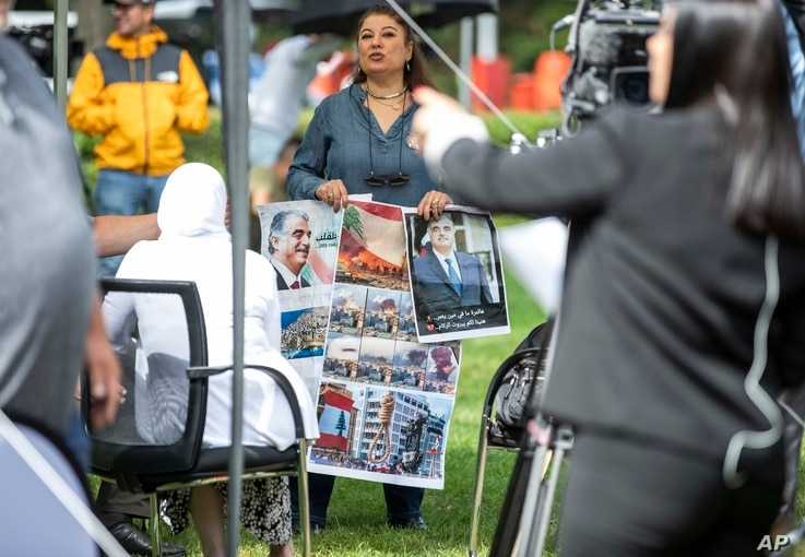 A woman holds images, some showing former Lebanon Prime Minister Rafik Hariri, outside the United Nations-backed Lebanon Tribunal in Leidschendam, Netherlands, Aug. 18, 2020.