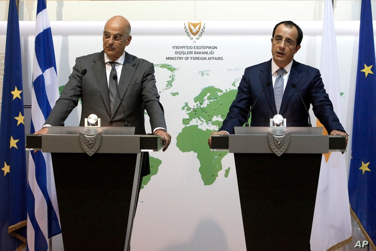 Greek foreign minister Nikos Dendias, left, and Cyprus' foreign minister Nikos Christodoulides talk during a press conference after their meeting at the Cyprus' foreign ministry in capital Nicosia, Cyprus, Aug. 18, 2020.