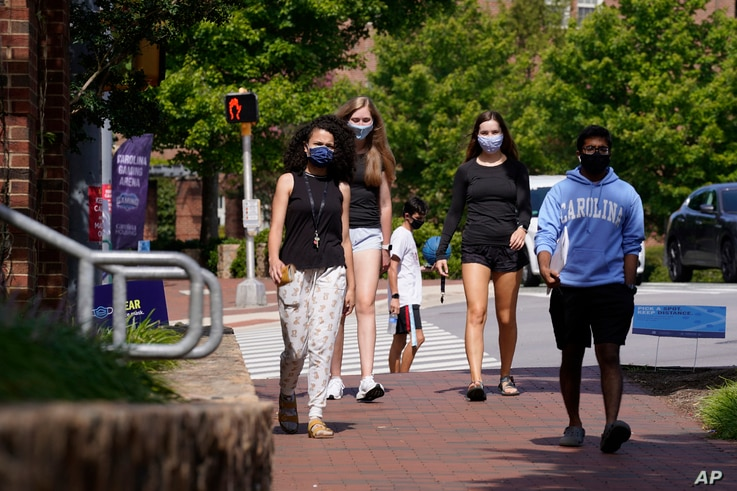 Students wear masks on campus at the University of North Carolina in Chapel Hill, N.C., Tuesday, Aug. 18, 2020. The university…