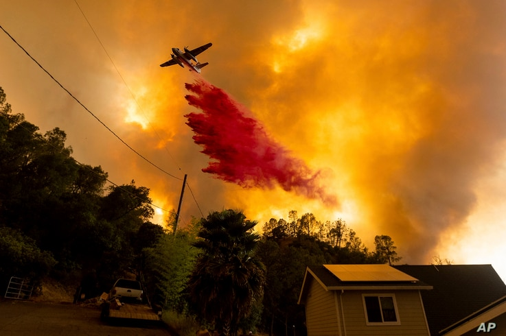 An air tanker drops retardant as the LNU Lightning Complex fires tear through the Spanish Flat community in unincorporated Napa…