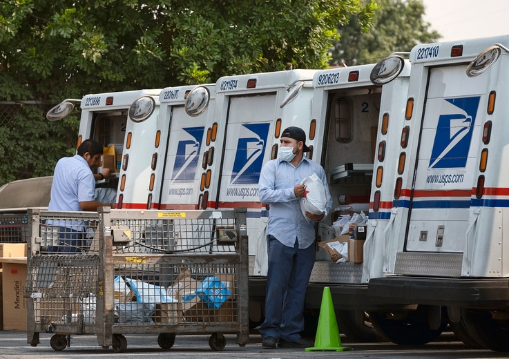 Postal workers load packages in their mail delivery vehicles at the Panorama city post office on Thursday, Aug. 20, 2020 in the…