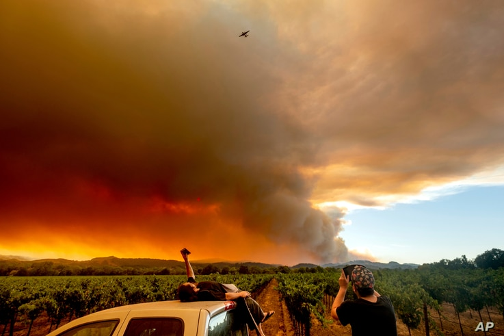 Thomas Henney, left, and Charles Chavira watch a plume spread over Healdsburg, Calif., as the LNU Lightning Complex fires burn,…