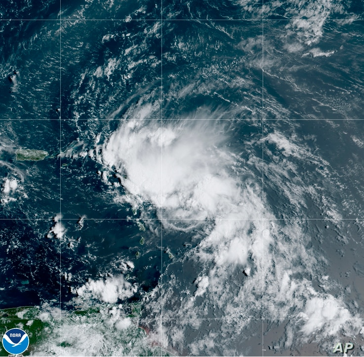 This satellite image released by the National Oceanic and Atmospheric Administration (NOAA) shows Tropical Storm Laura in the…