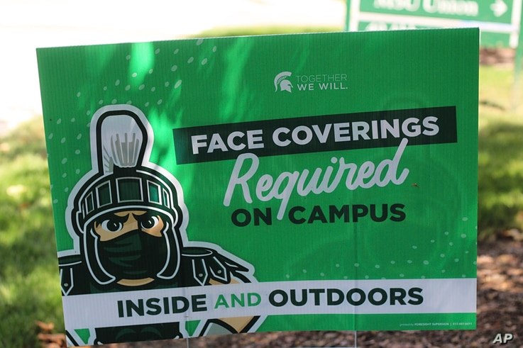 A sign outside the Michigan State University Student Union building alerts students to MSU's face covering rule on Friday, Aug…