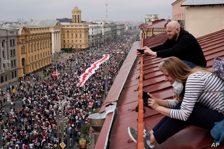 People take photos sitting on the roof as Belarusian opposition supporters with a huge old Belarusian national flag march to Independence Square in Minsk, Belarus, Aug. 23, 2020.