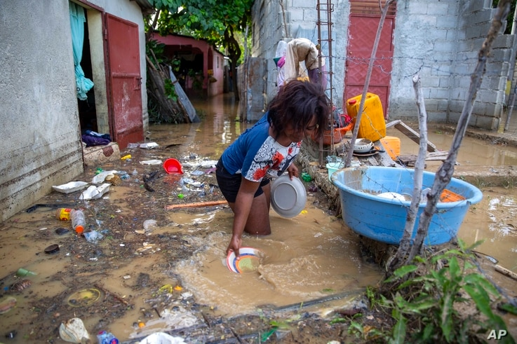 Yoleine Toussaint 22, removes mud from plates in front of her flooded house, one day after the passing of Tropical Storm Laura,…