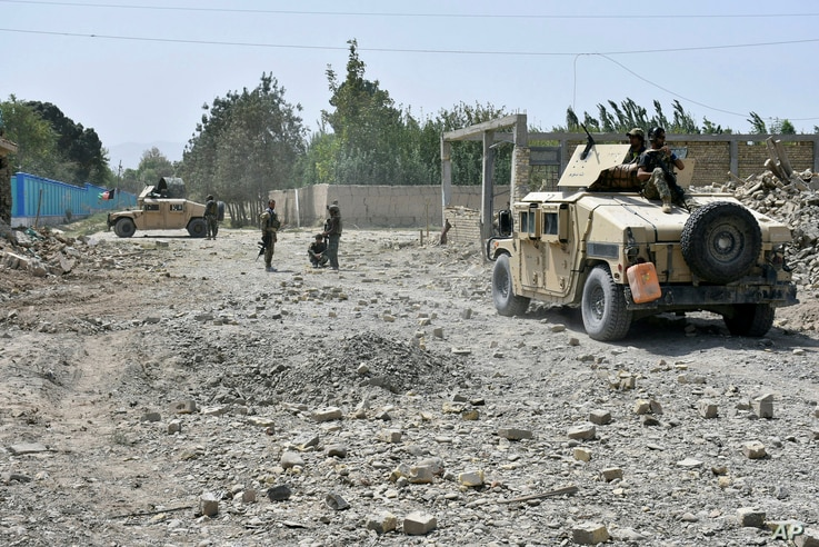 Afghan Security personnel inspect the site of truck suicide bombing in the northern Balkh province of Afghanistan, Tuesday, Aug…
