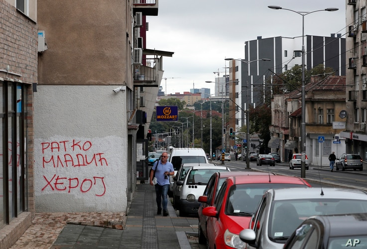 A man walks past a graffiti that reads 'Ratko Mladic Hero' in Belgrade, Serbia, Tuesday, Aug. 25, 2020. A lawyer for Ratko…