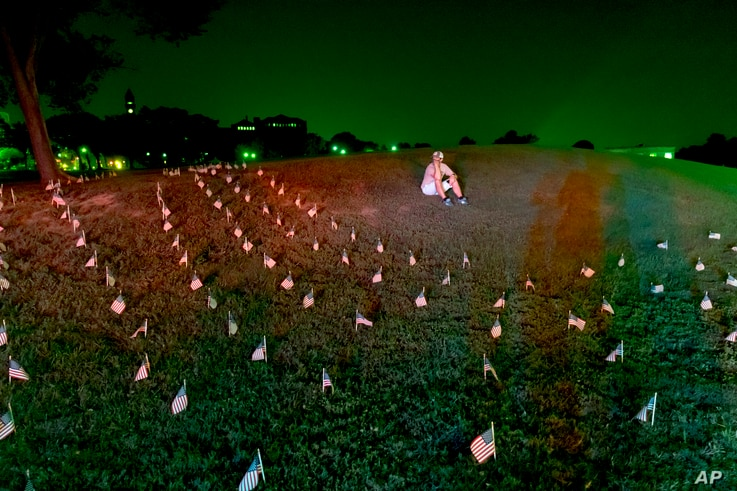 An activist sits among flags placed near the Washington Monument to memorialize the 180,000 people who have died in from the Covid-19 pandemic in the U.S. Aug. 27, 2020, in Washington.