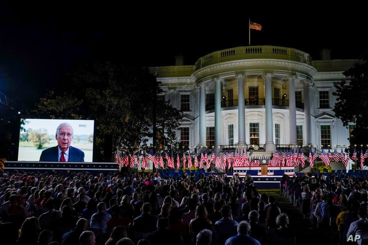 People watch video screens before President Donald Trump speaks from the South Lawn of the White House.