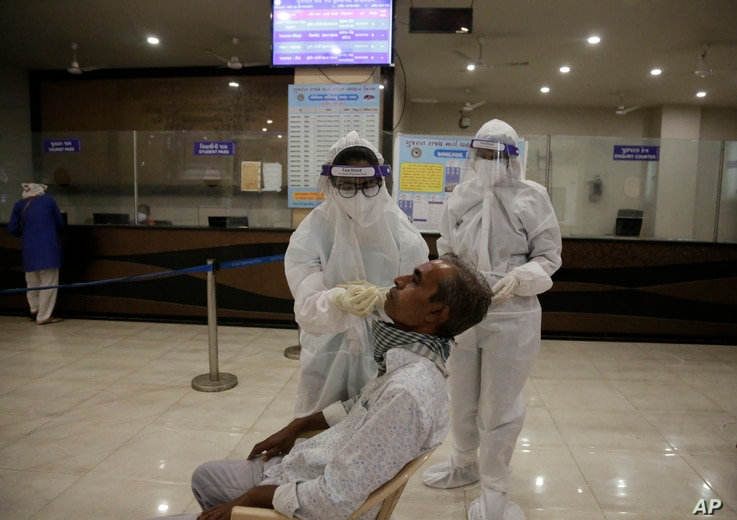 A health worker takes a nasal swab sample to test for COVID-19 at a state bus station in Ahmedabad, India, Aug. 29, 2020.