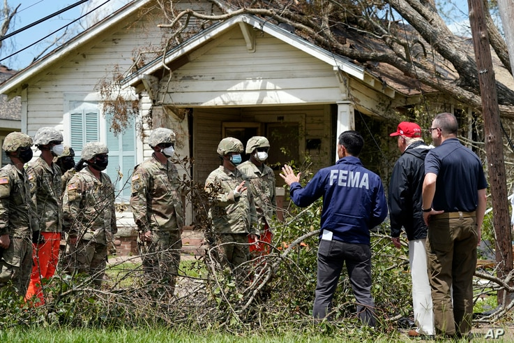President Donald Trump and Homeland Security Secretary Chad Wolf speak with National Guard soldiers helping with cleanup as…