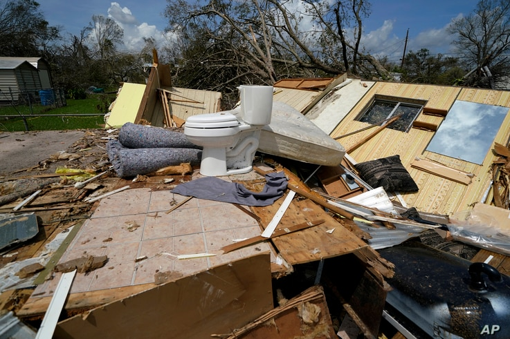 Remnants of the half destroyed mobile home of James Towfley, who is living in the standing half, are seen in Lake Charles, La.,…