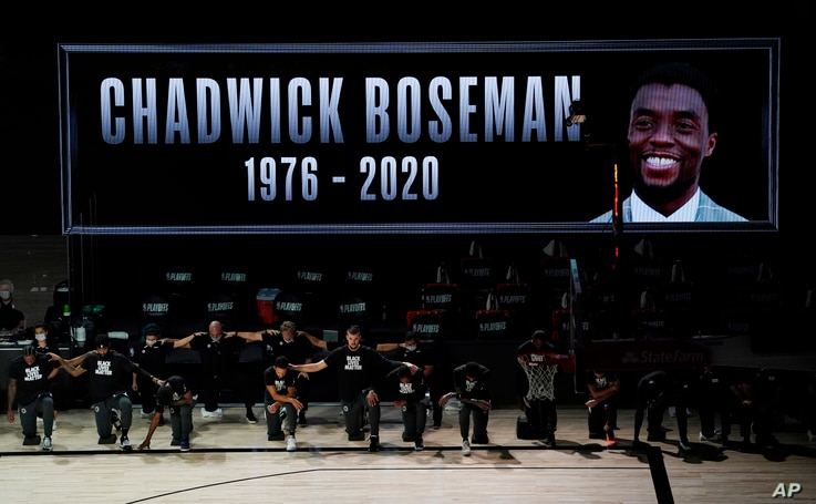 The Los Angeles Clippers kneel to pay respect to the Black Lives Matters movement while a photo of actor Chadwick Boseman is…