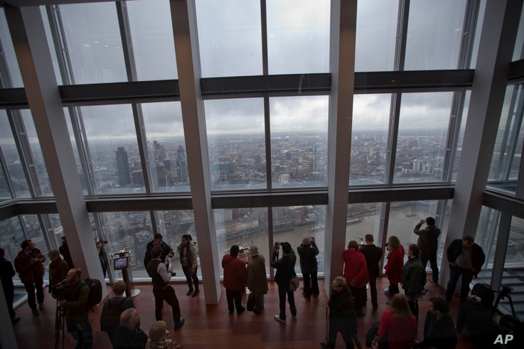 "FILE - Visitors look at the sights during the official opening of ""The View"" viewing platform at the Shard skyscraper in London."