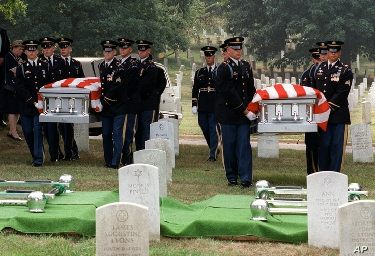 An Army honor guard carries the caskets of Julian Bartley Jr., left, and his father Julian Bartley Sr. during funeral services…