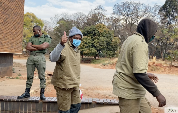 Journalist Hopewell Chin'ono gives a thumbs-up to reporters as he leaves Harare Magistrates Court,  Aug. 7, 2020, after launching a third bail application. (Columbus Mavhunga/VOA)