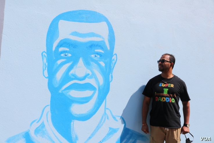 Ruhel Islam, owner of Gandhi Mahal Restaurant, poses next to a mural of George Floyd located across the street from the ruins of the restaurant. Despite losing his restaurant, Islam continues to support the Black Lives Matter movement. (K. Khan/VOA)