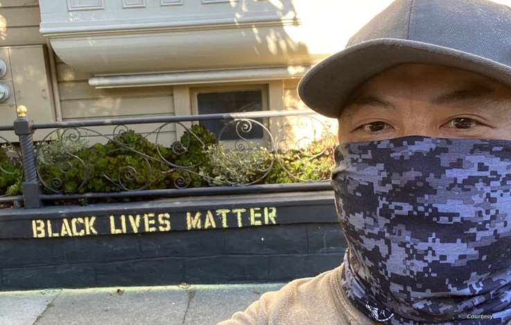"James ""Jaime"" Juanillo stands in front of the Black Lives Matter wall art that prompted a woman to question whether he was defacing private property at his San Francisco home. (Courtesy James Juanillo)"