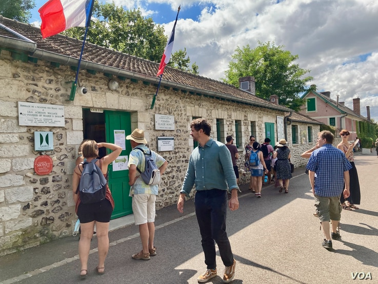 Tourists check out opening hours at Claude Monet's house, which reopened in June following France's two-month coronavirus lockdown. (Photo: Lisa Bryant/VOA)
