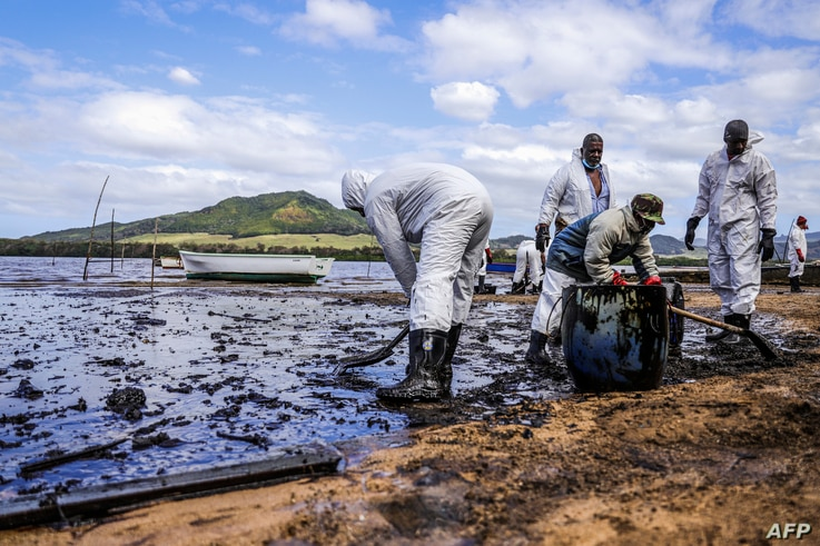 People scoop leaked oil from the vessel MV Wakashio, belonging to a Japanese company but Panamanian-flagged, that ran aground and caused oil leakage near Blue bay Marine Park in southeast Mauritius, Aug. 9, 2020.