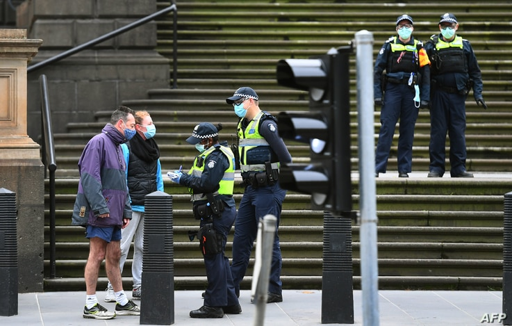 Police check details of residents in the Melbourne central business district on August 9, 2020.