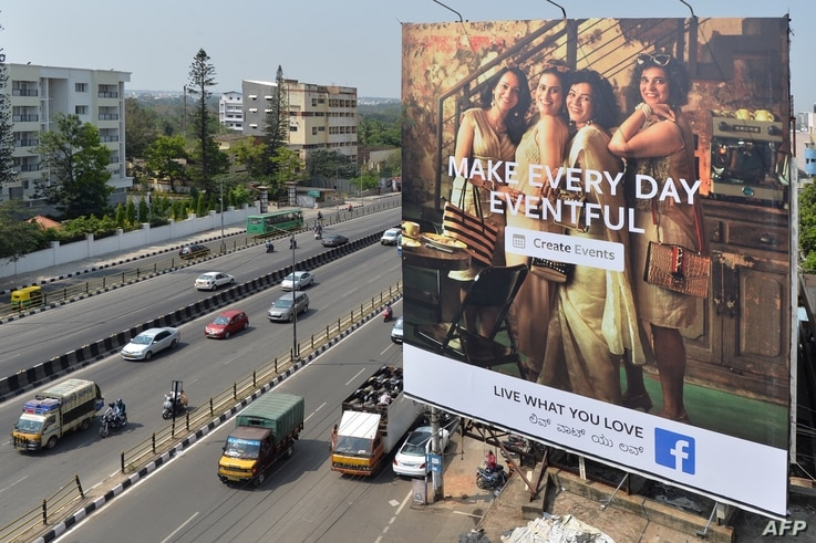 FILE - Indian commuters pass a poster of a Facebook ad campaign, in Bangalore, India, March 22, 2018.