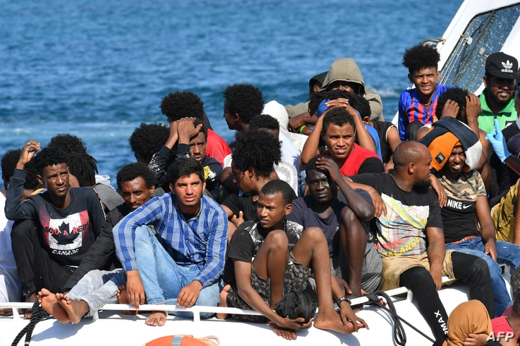 Migrants from Tunisia and Lybia arrive onboard an Italian Guardia Costiera (Coast Guard) boat on the Italian Pelagie Island of Lampedusa, Aug. 1, 2020.