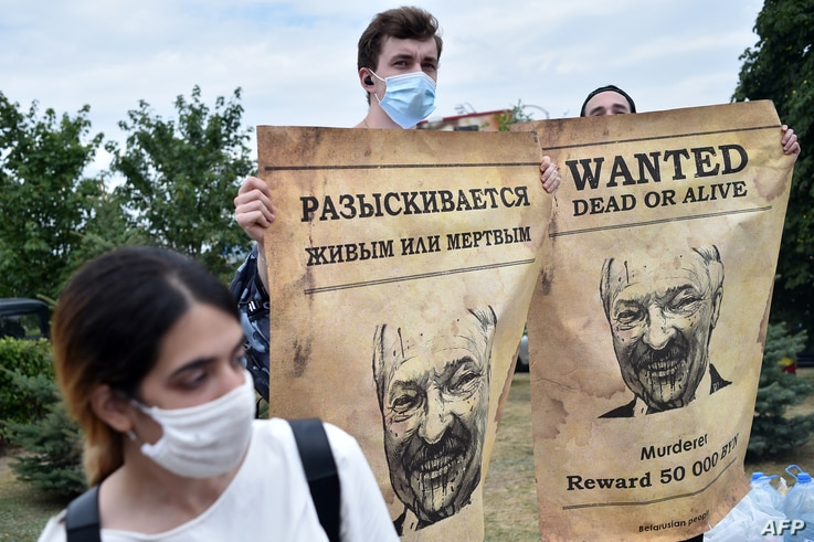 """Opposition supporters hold up """"Wanted"""" posters with images of Belarusian President Alexander Lukashenko during protests over the country's disputed presidential election, in Minsk, August 18, 2020."""